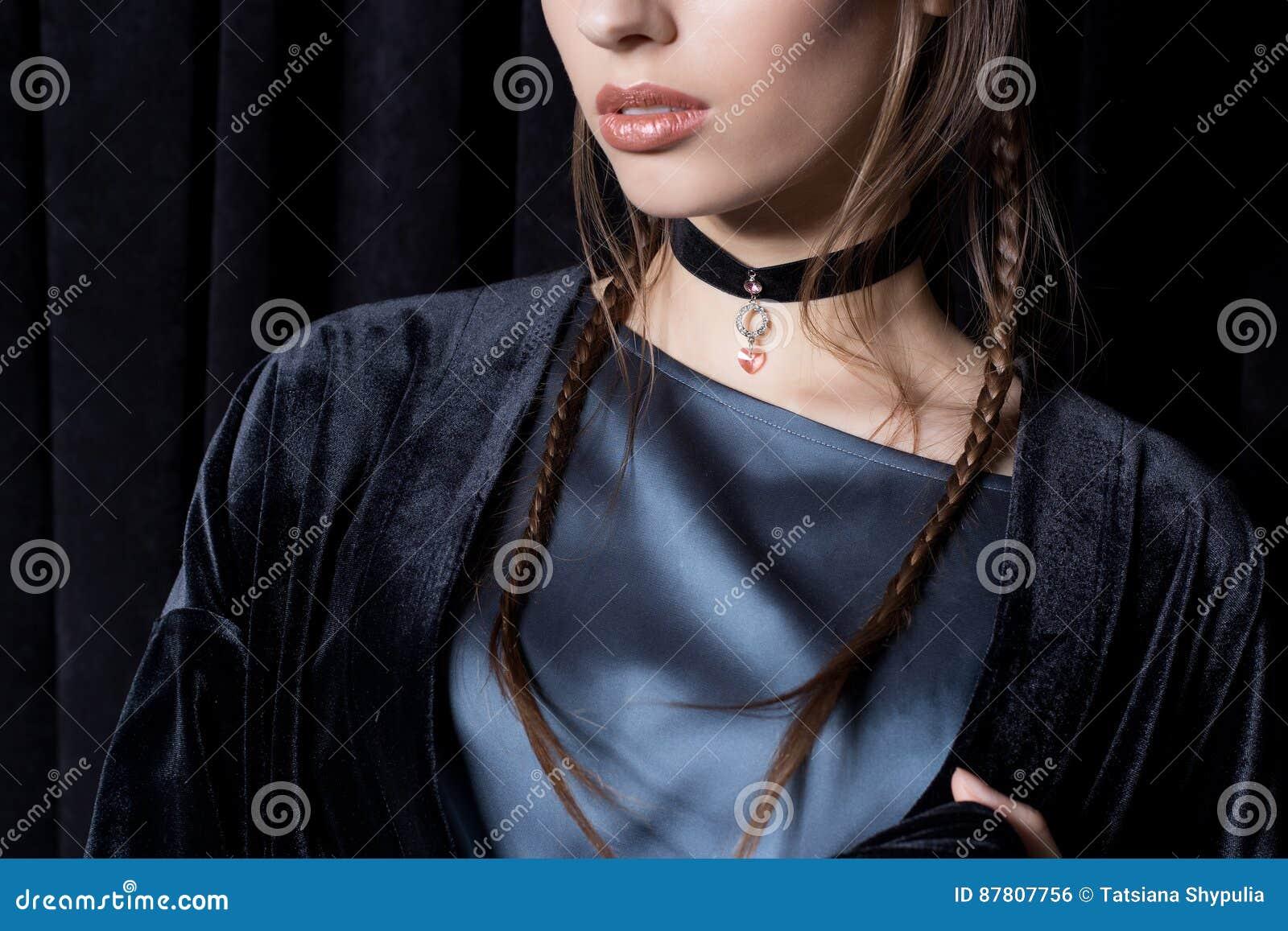 Härlig sexig ung kvinna med mörkt hår som flätas med den ljusa makeup- och modesmyckentättsittande halsband runt om hennes hals,