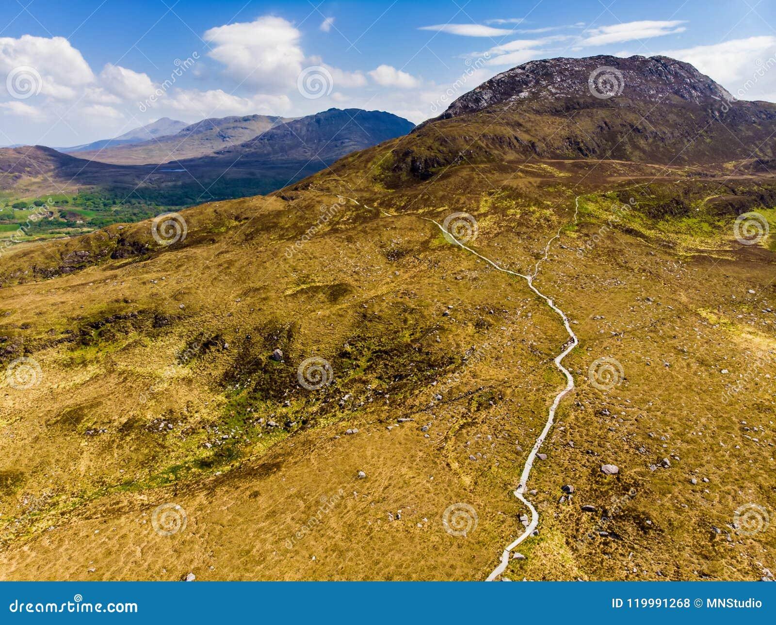 Härlig sikt av den Connemara nationalparken som är berömda för myrar och heder, hållet ögonen på över av dess konformade berg, Di