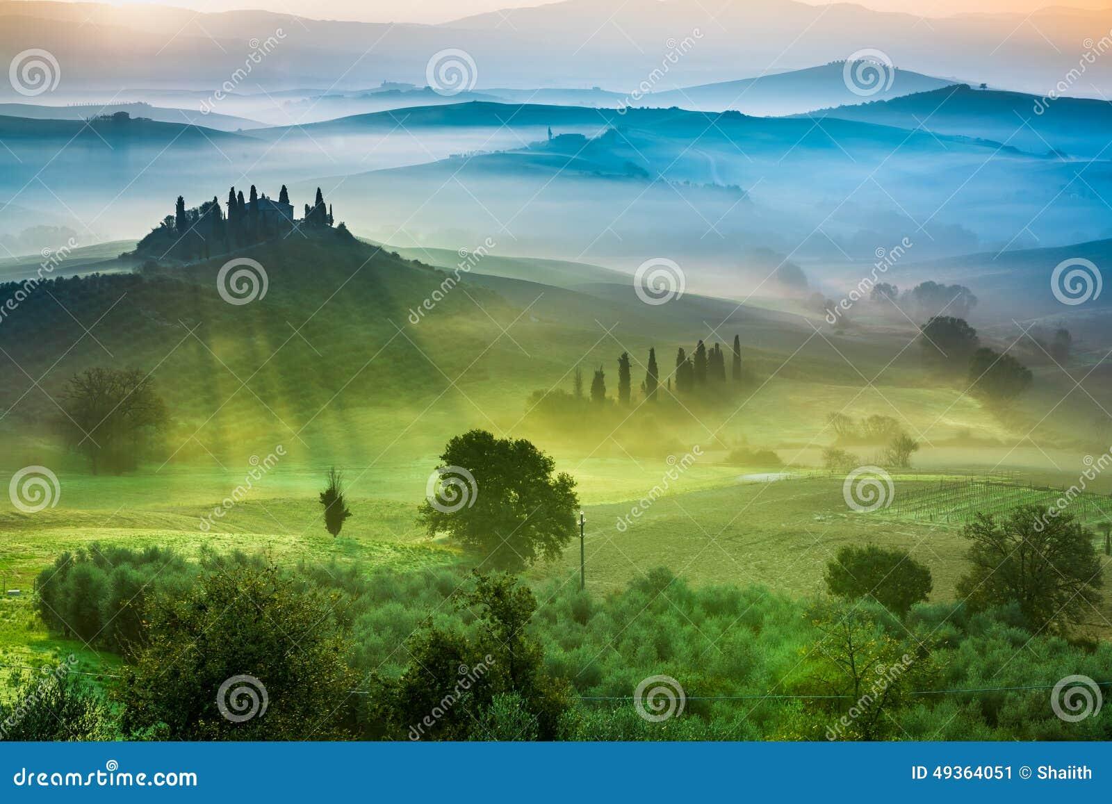 Härlig sikt av gräsplanfält och ängar på solnedgången i Tuscany