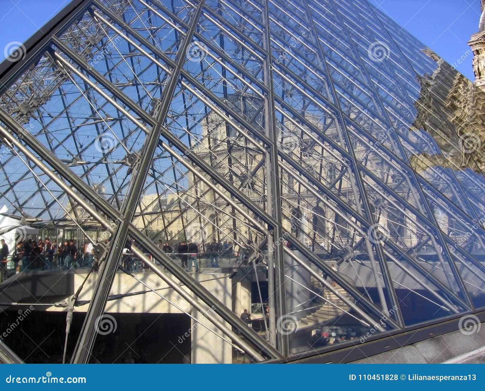 Härlig sikt av Louvre - pyramiden glasade trappa och folk som inom genomreser