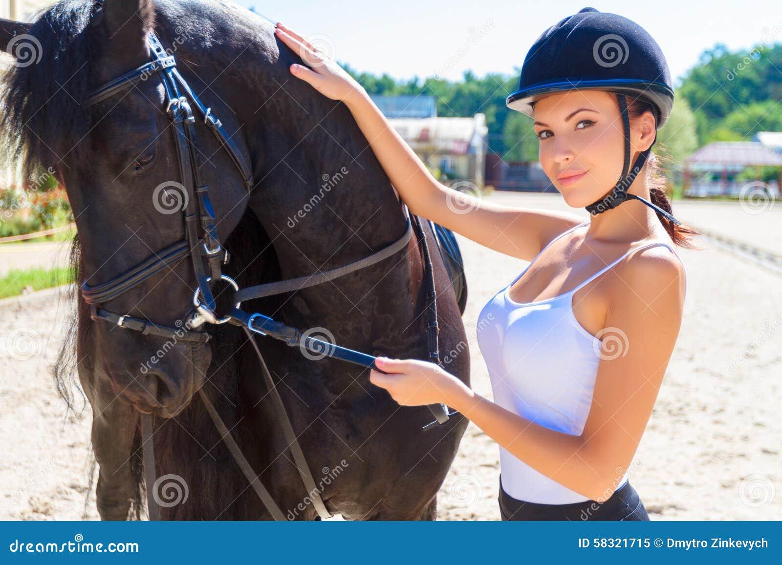 Härlig skicklig ryttarinna med en häst