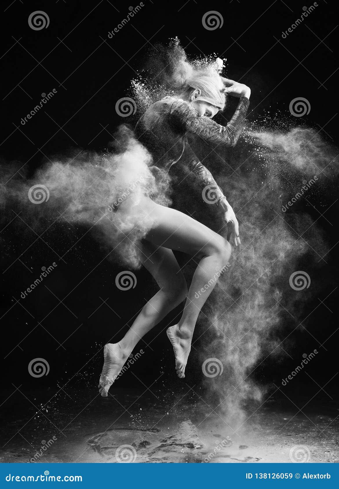 Härlig slank flicka som bär en gymnastisk bodysuit som täckas med moln av de vita pulverhoppen för flyga som dansar på ett mörker