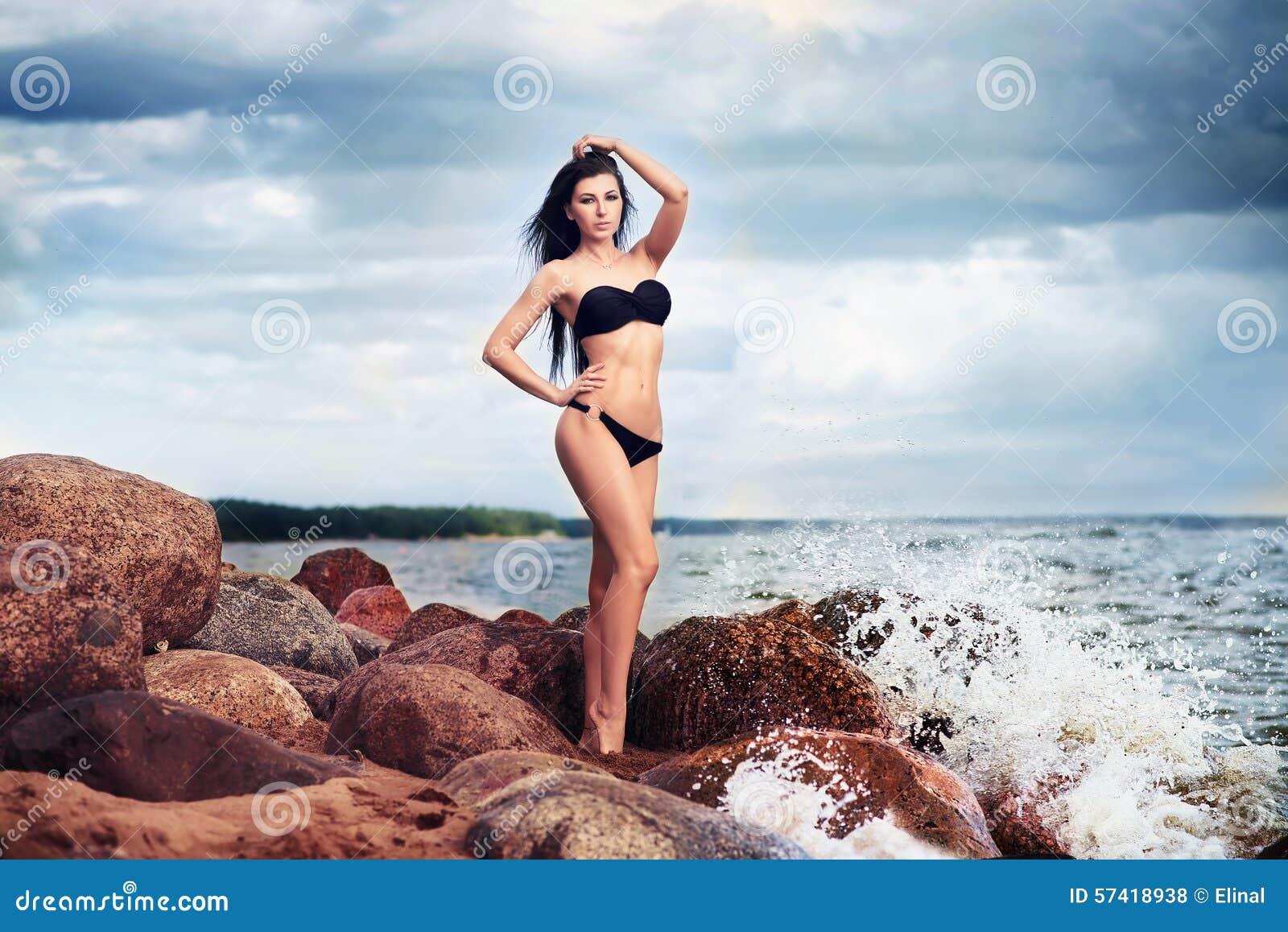 Härlig slank kvinna i svart bikini Strand, sand och stenar