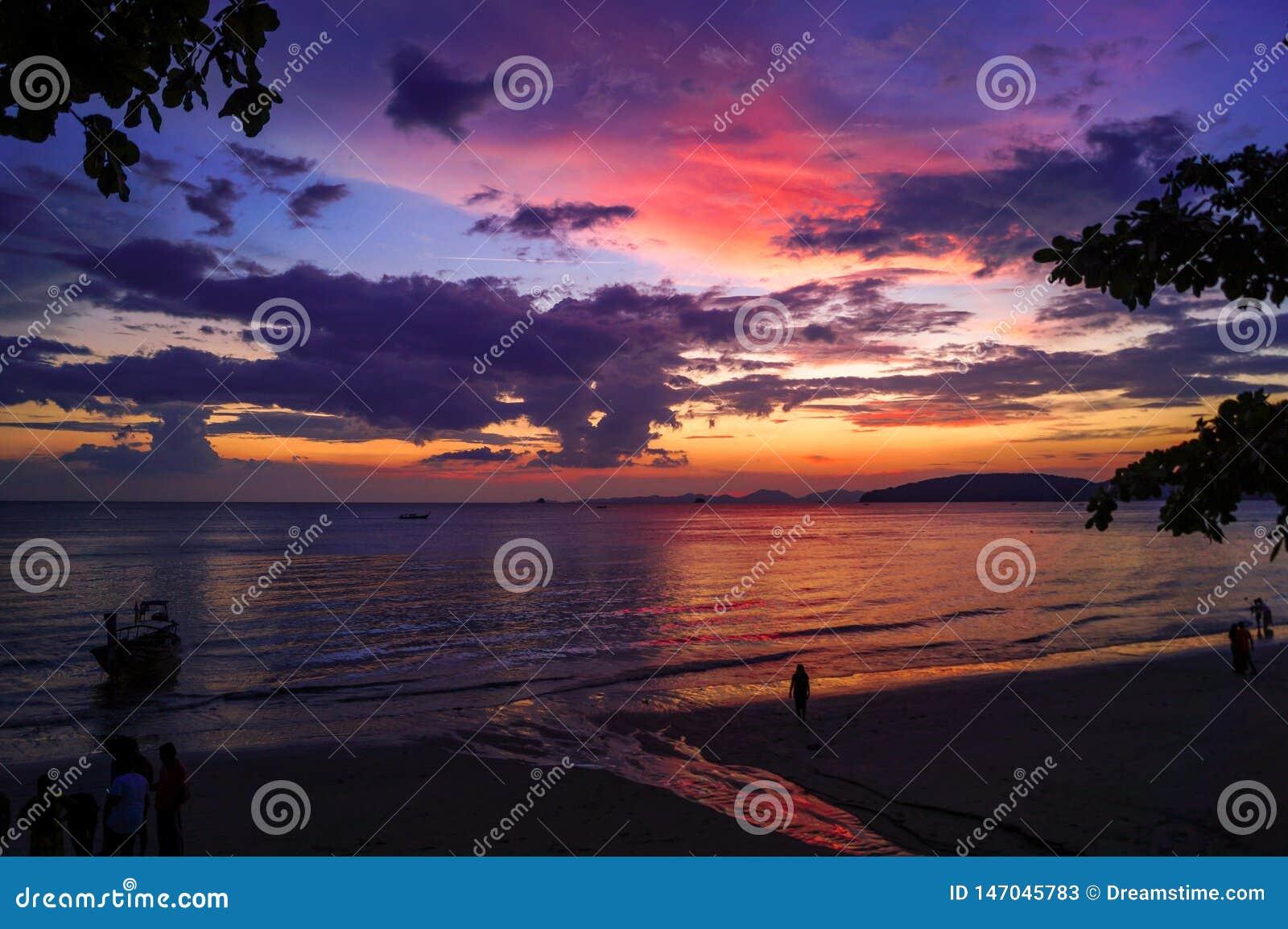 Härlig solnedgång med röda, purpurfärgade och gula färger på stranden i Thailand