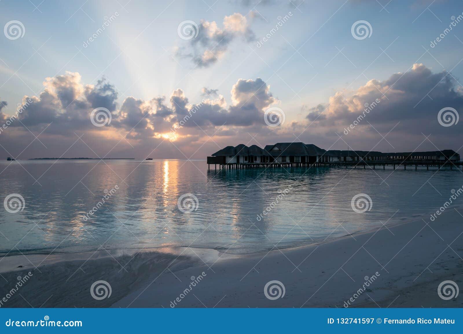 Härlig solnedgång på stranden som förbiser vattenbungalowerna i Maldiverna