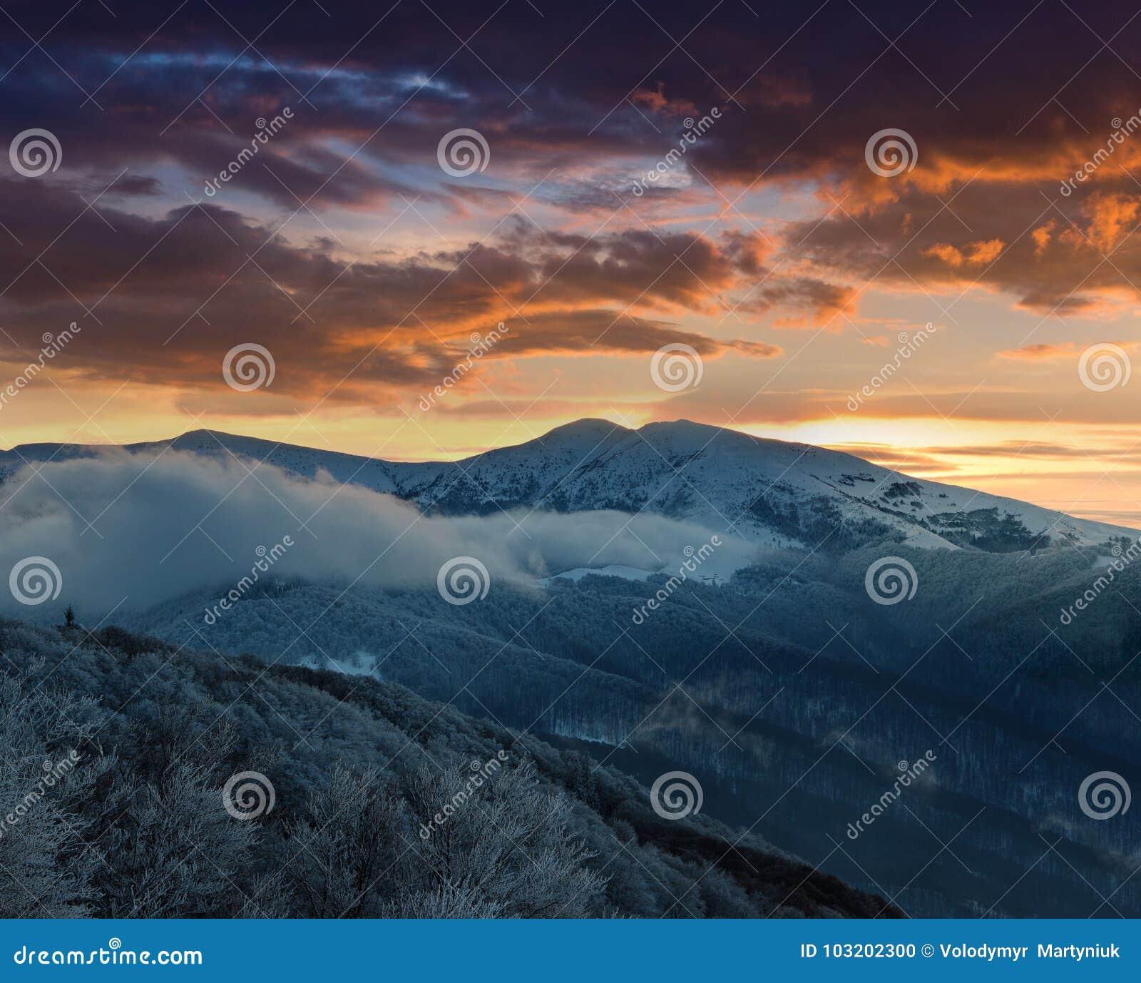 Härlig soluppgång i vinterbergen Dramatisk molnig over himmel
