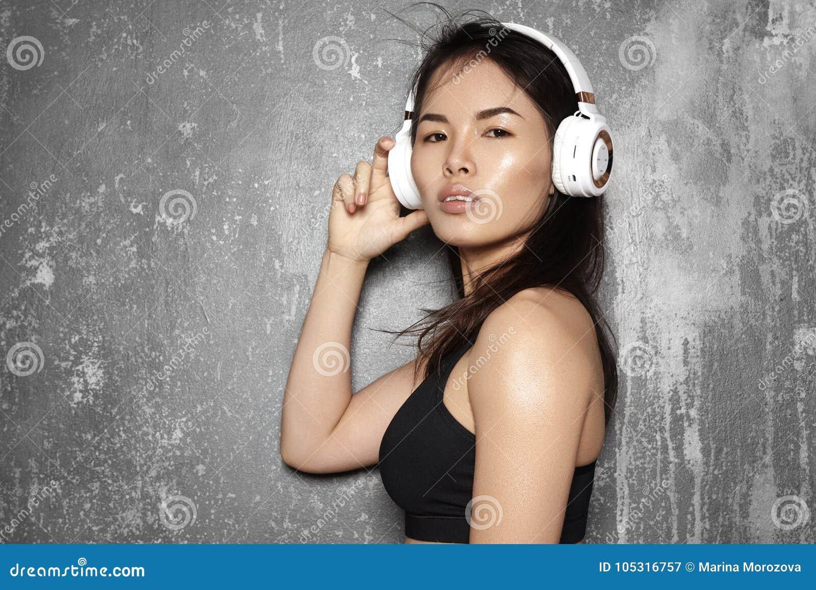 Härlig sportkvinna med stor vit hörlurar Modell som lyssnar musiken Konditionstående, perfekta kroppformer