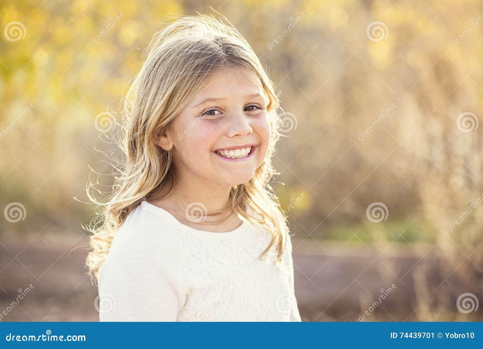 Härlig stående av att le lilla flickan utomhus
