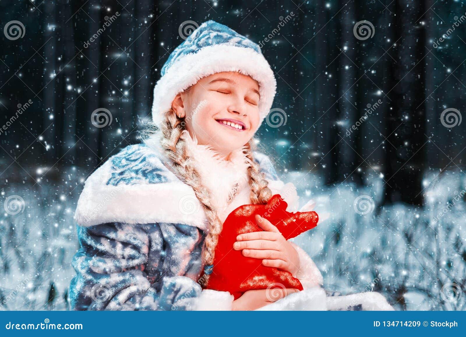 Härlig stående av snöjungfrun i en festlig dräkt den lyckliga lilla flickan rymmer påsen för det nya året med gåvor sagolik vinte