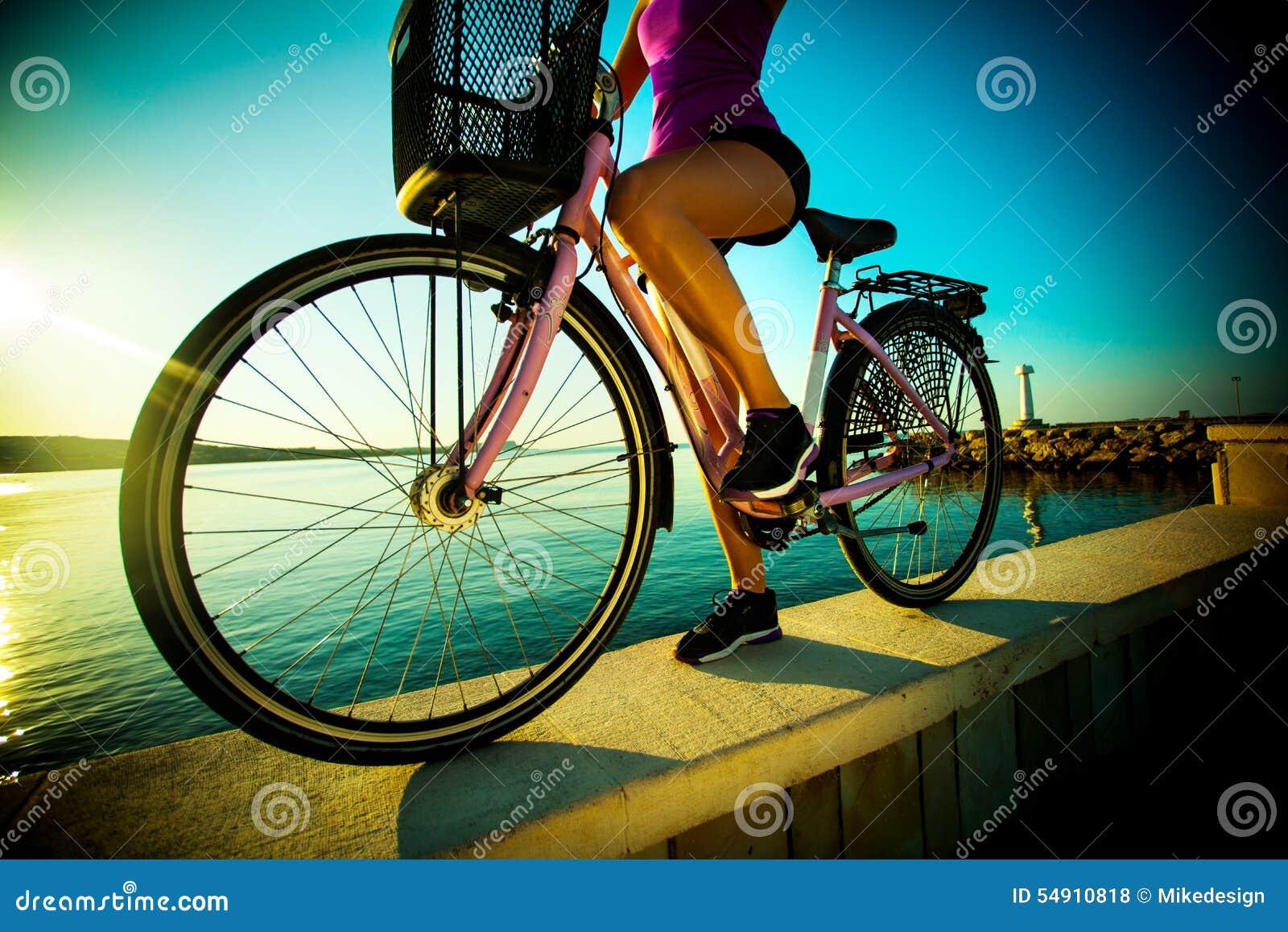 Härlig streightkvinna med cykeln på solnedgång