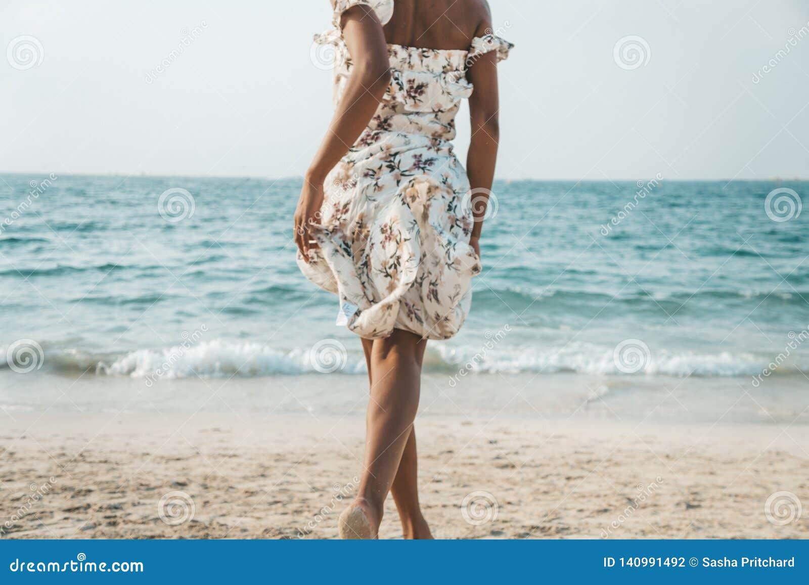 Härlig svart kvinna som kör till havet på stranden