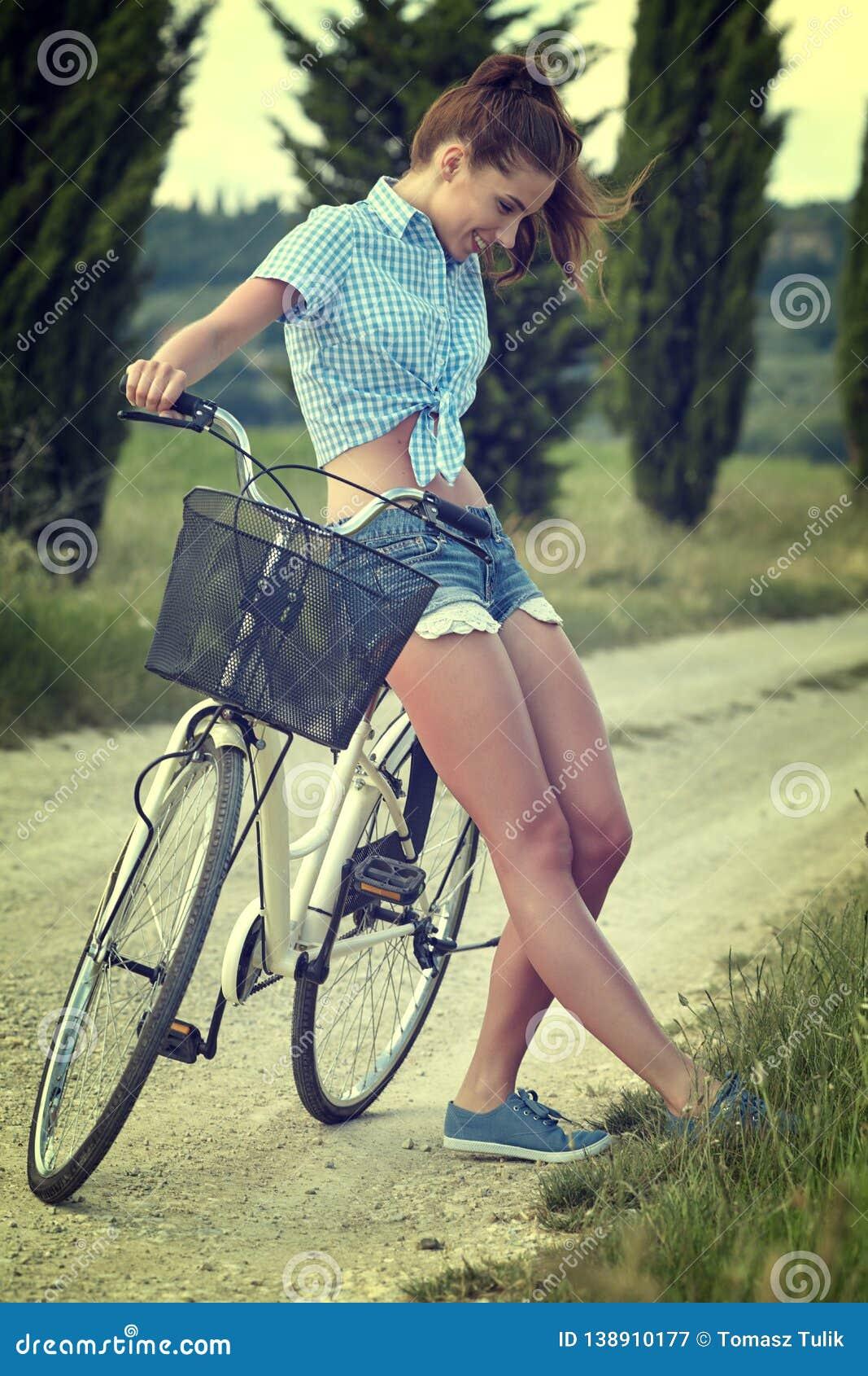 Härlig tappningflicka som sitter bredvid cykeln, sommartid