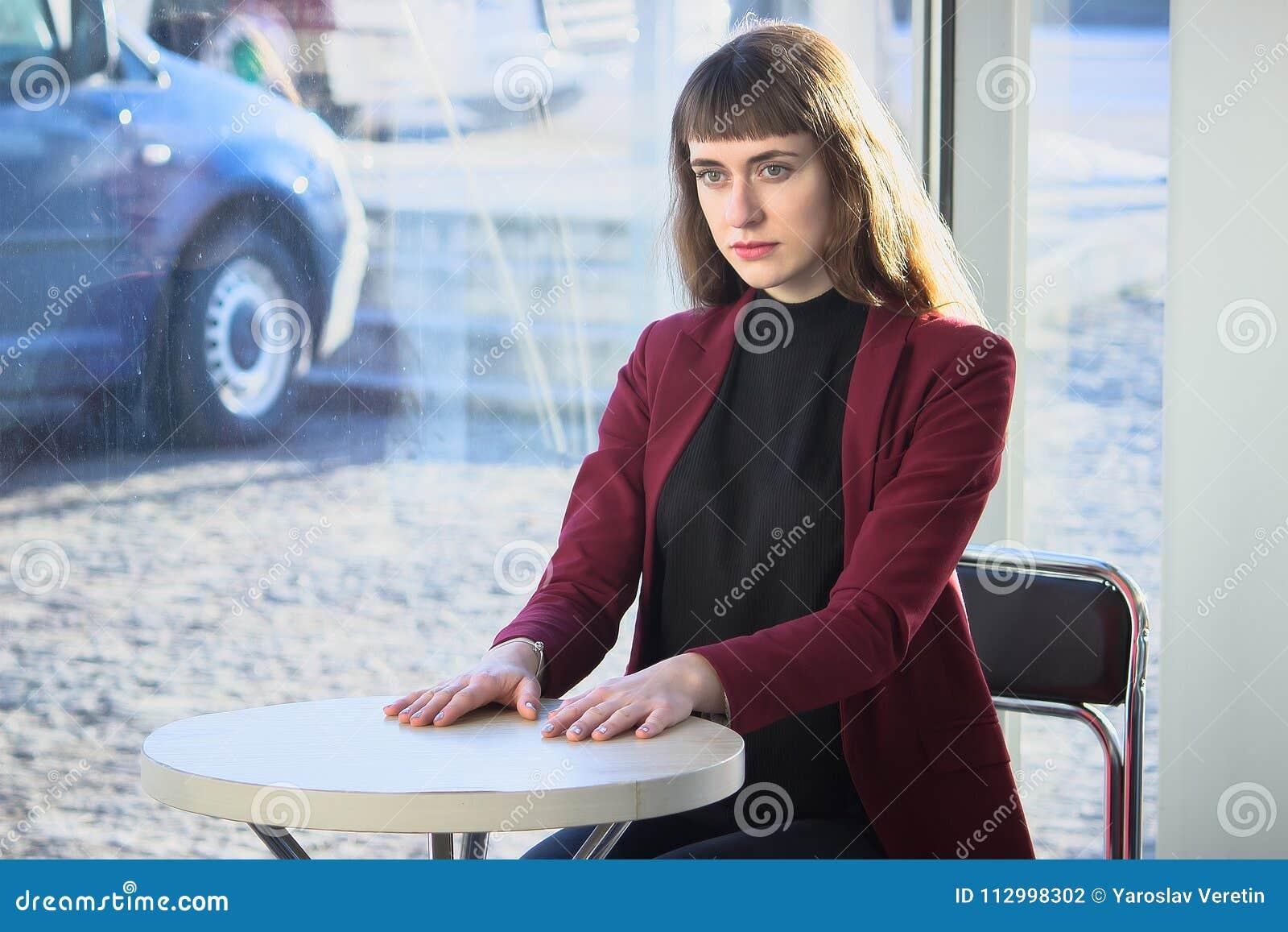 Härlig trendig flicka på en tabell i ett kafé