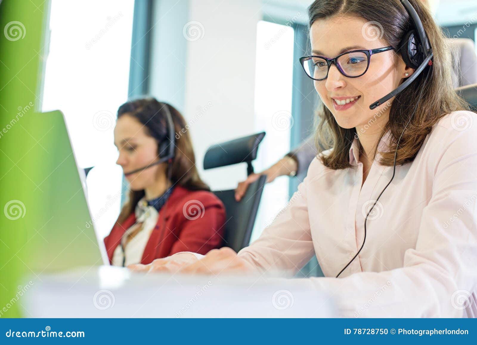 Härlig ung affärskvinna som använder hörlurar med mikrofon med kollegor i bakgrund på kontoret