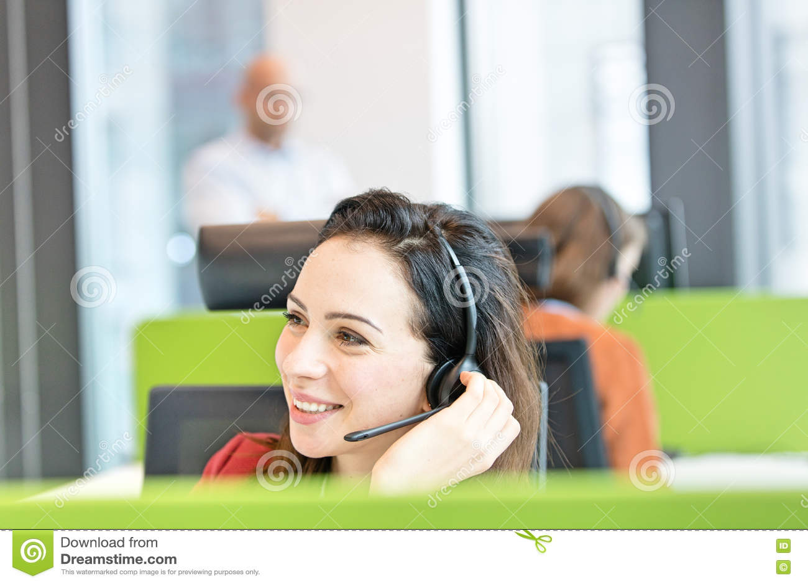 Härlig ung affärskvinna som i regeringsställning använder hörlurar med mikrofon