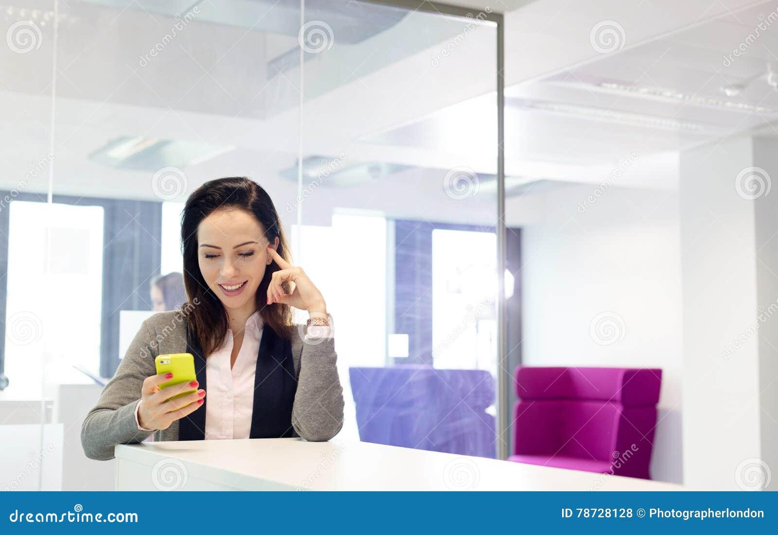 Härlig ung affärskvinna som i regeringsställning använder mobiltelefonen