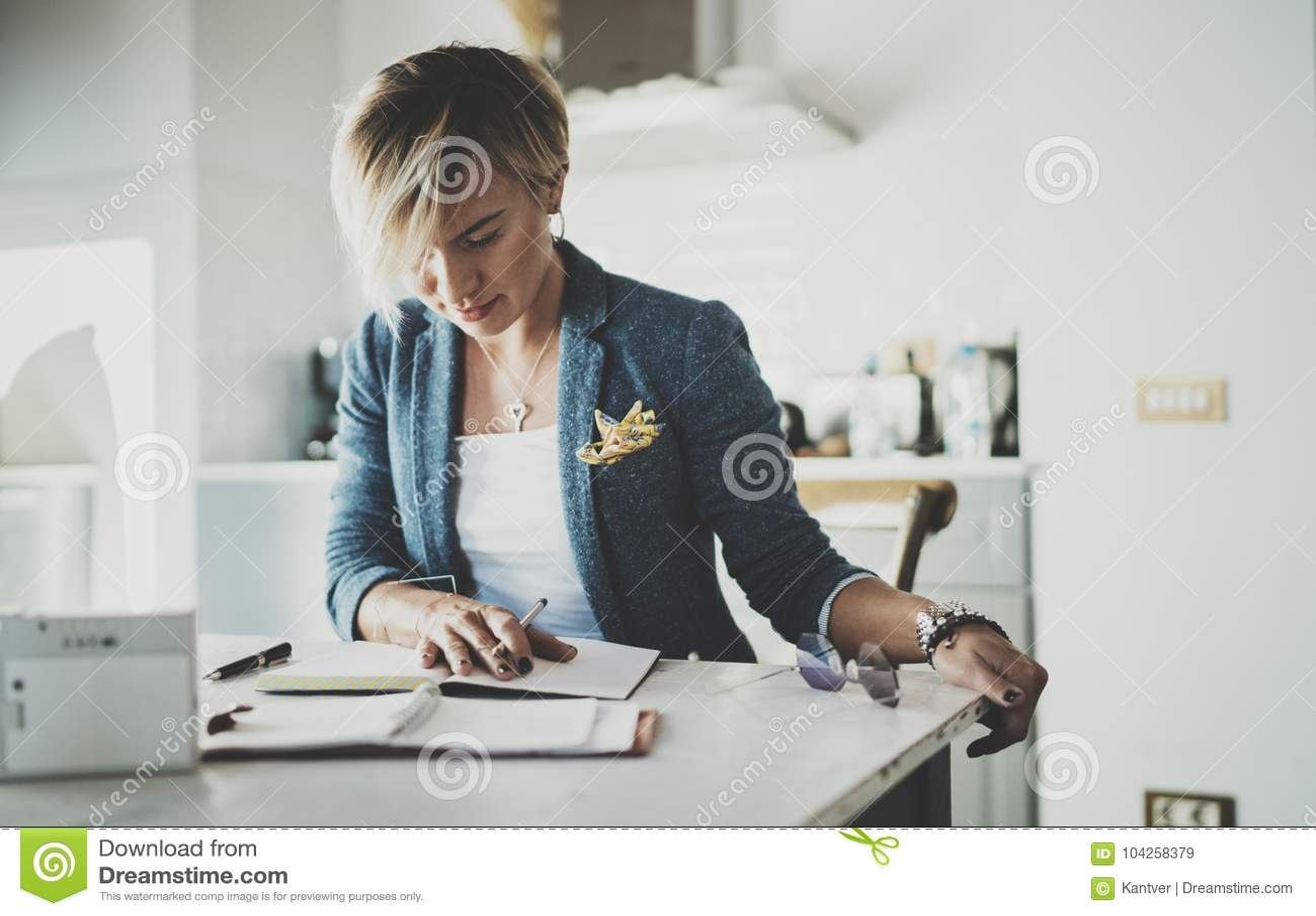 Härlig ung affärskvinnahandstil något i anteckningsbok, medan sitta på fåtöljen på vardagsrum charmig kvinnlig