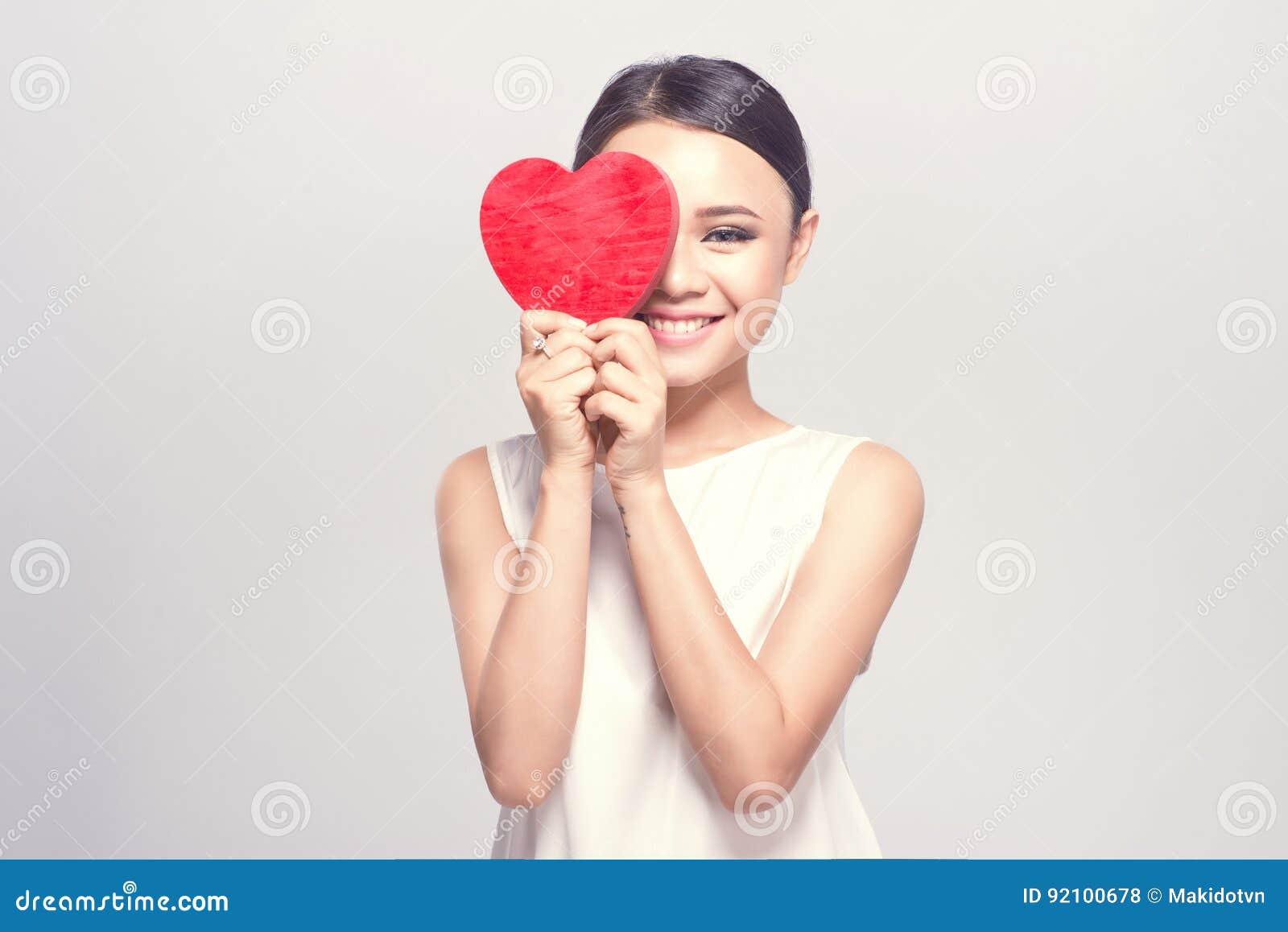 Härlig ung asiatisk kvinna som rymmer röd hjärta på vit