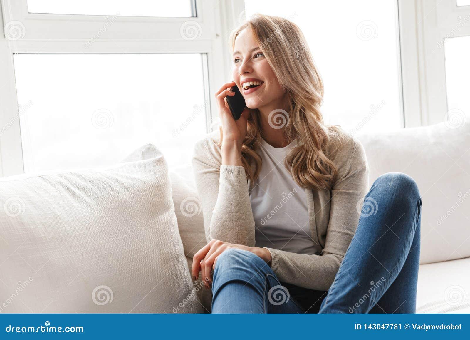 Härlig ung blond kvinna som kopplar av på en soffa