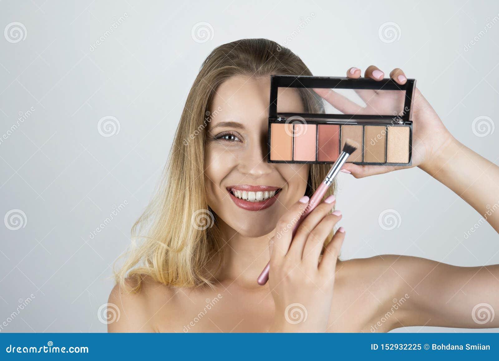 Härlig ung blond kvinnainnehavpalett som applicerar ögonskugga på den borste isolerade vita bakgrunden