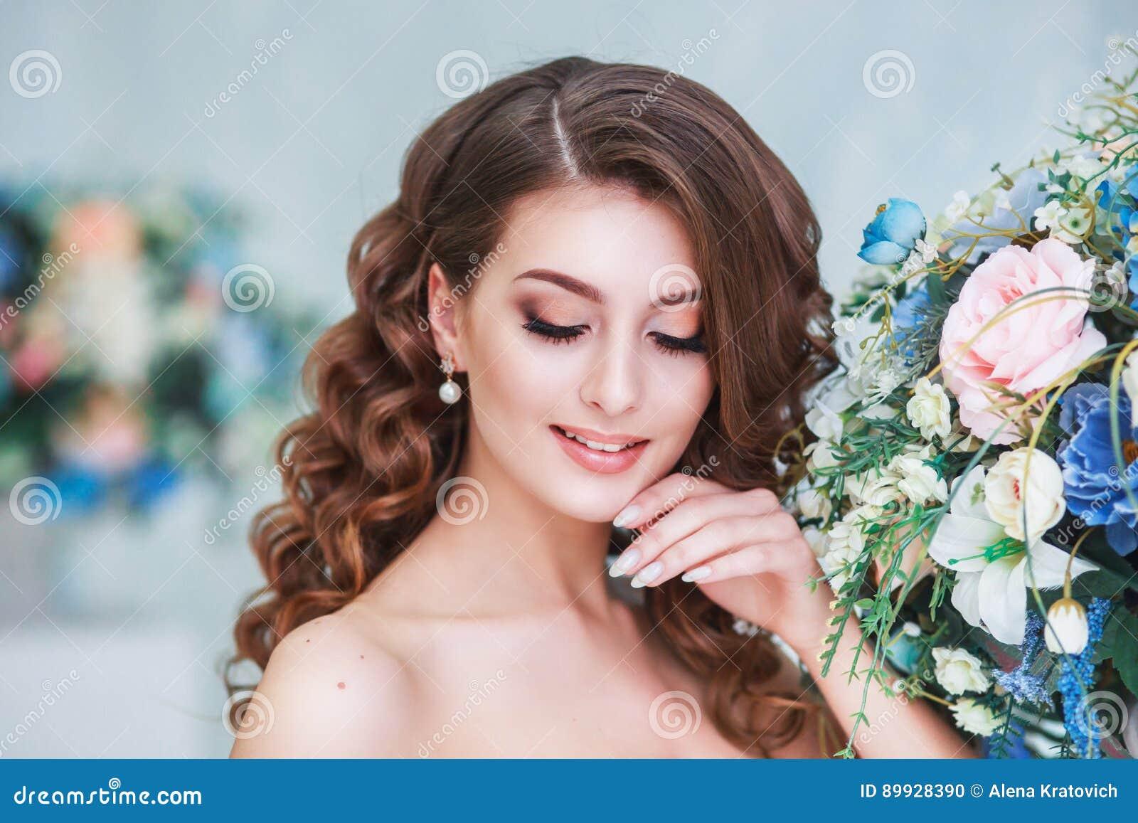 Härlig ung brud med den bröllopmakeup och frisyren inomhus Closeupstående av den unga ursnygga bruden i studio