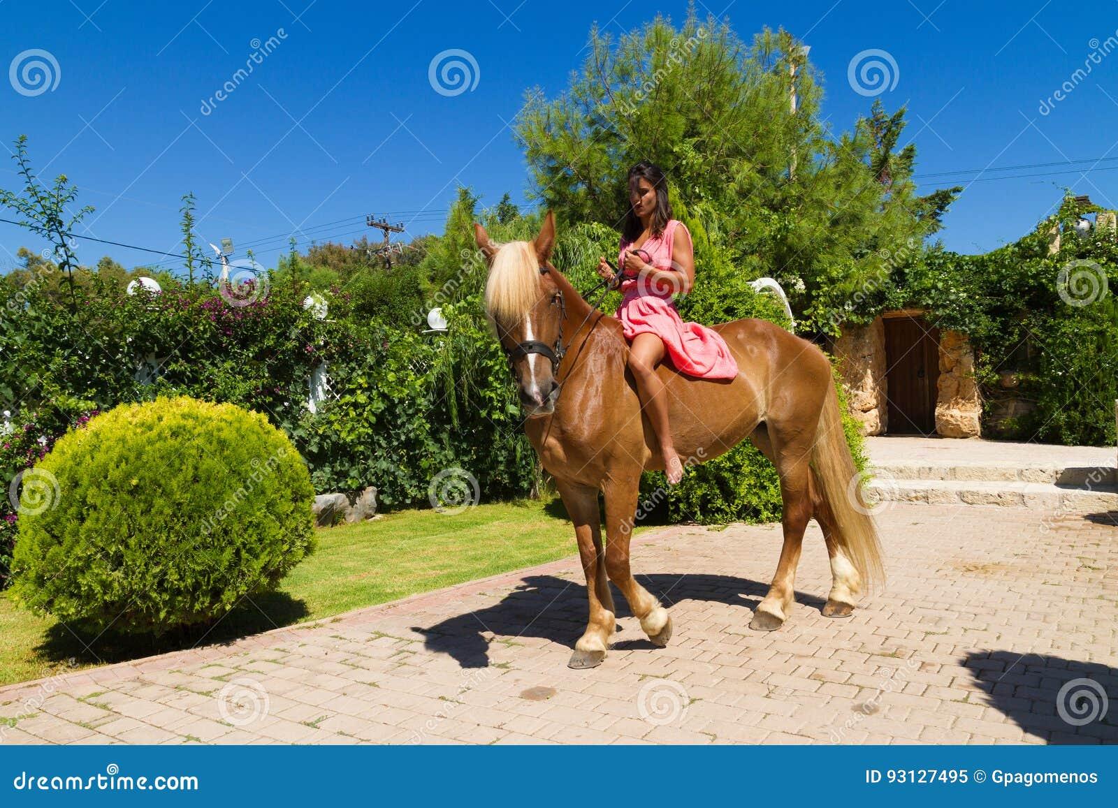 Härlig ung brunett med den röda klänningen och hennes brunt-blonda hors