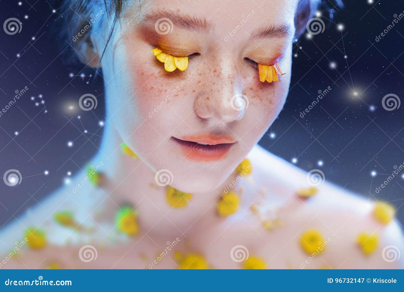 Härlig ung flicka i bilden av flora, närbildstående Sagolik stående på en stjärnklar bakgrund