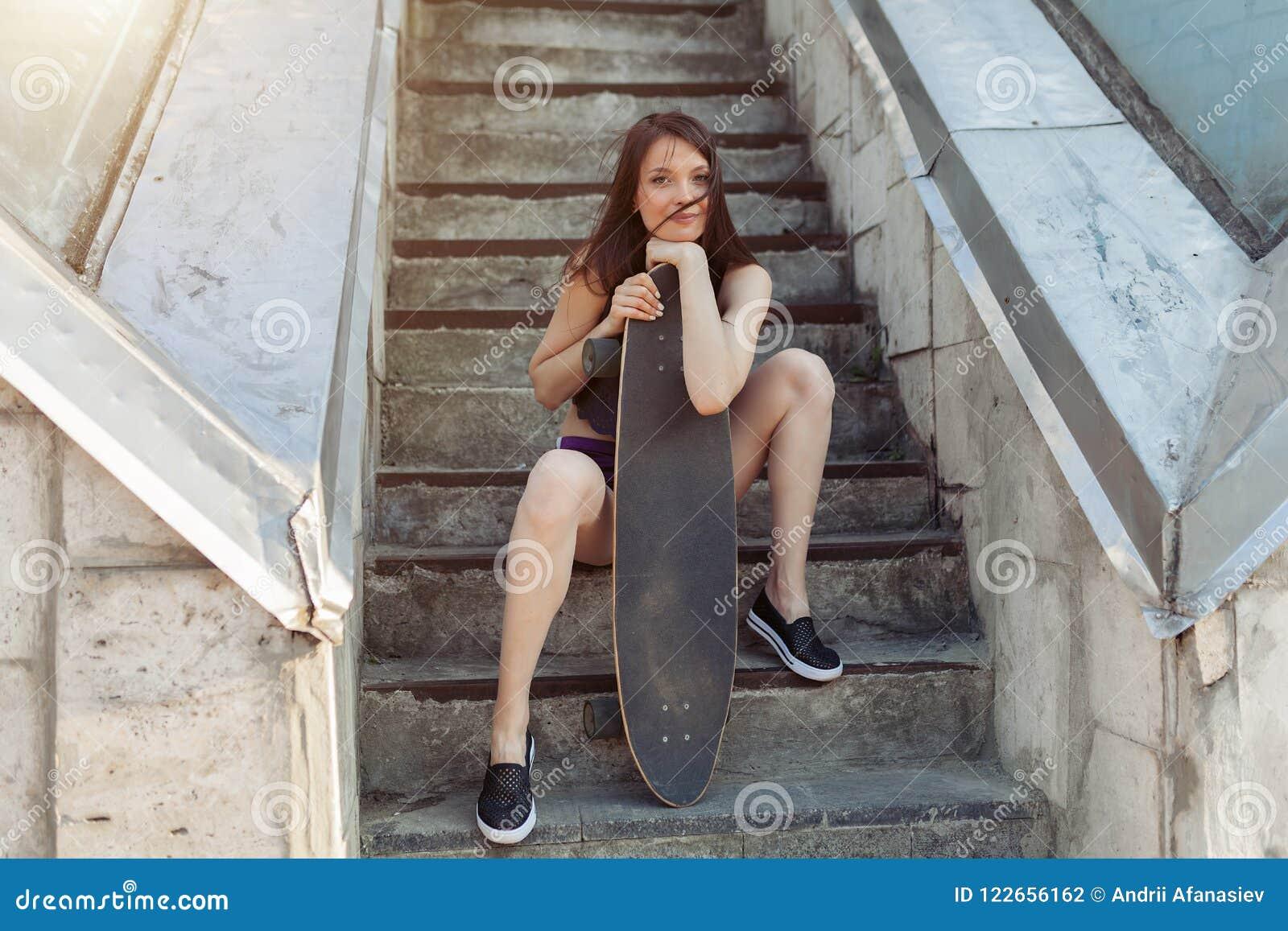 Härlig ung flicka med ett långt bräde i staden Begreppet av modern ungdom Aktiv rolig ferie