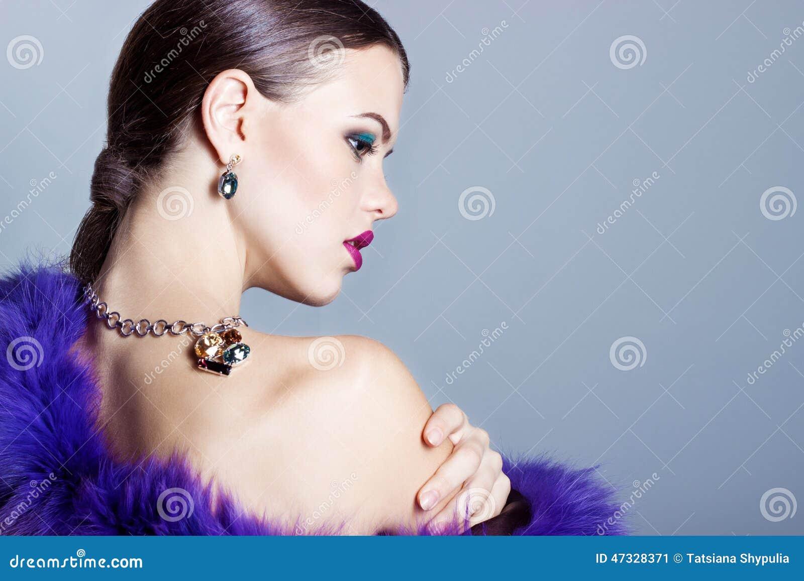 Härlig ung flicka med härliga stilfulla dyra smycken, halsband, örhängen, armband, cirkel som filmar i studion