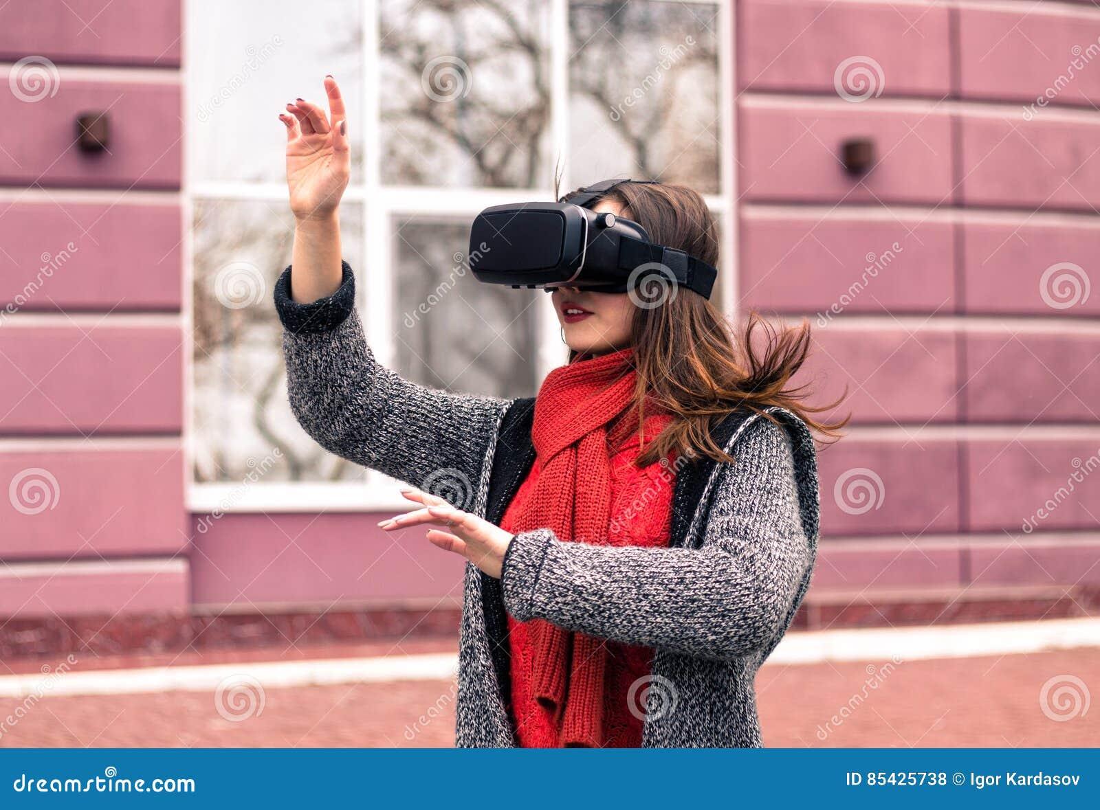 Härlig ung flicka med virtuell verklighethörlurar med mikrofon eller exponeringsglas 3d