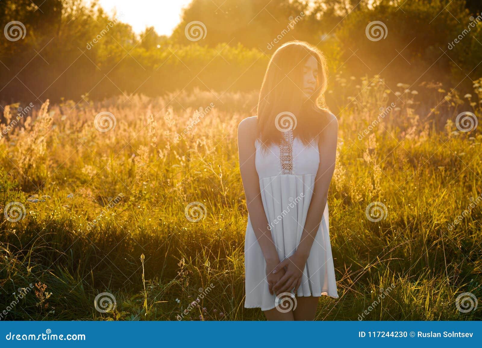 Härlig ung flicka som utomhus går i aftonen