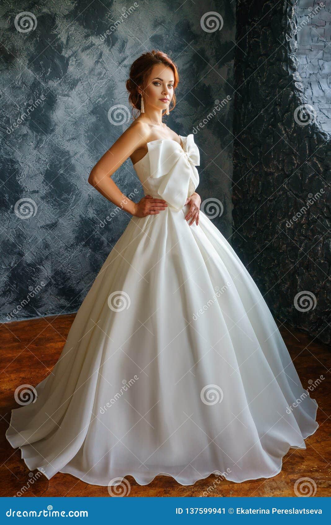 Härlig ung kvinna i bröllopsklänning, romantisk bild av bruden, härligt smink och frisyr