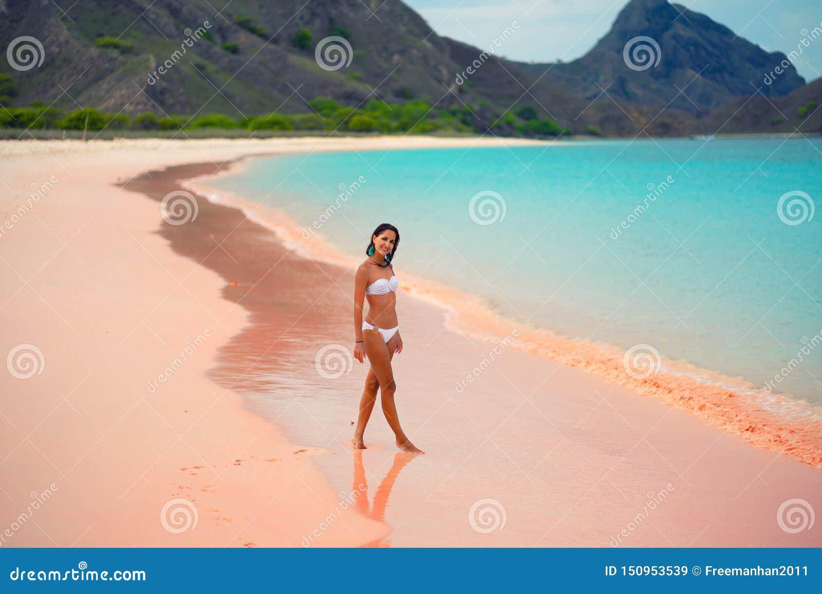 Härlig ung kvinna i den vita bikinin som poserar på den rosa stranden, ö Lombok, Bali