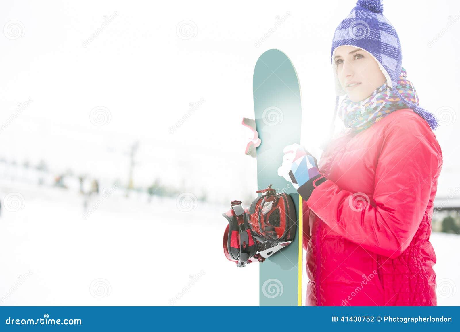 0b518341185 Härlig Ung Kvinna I Hållande Snowboard För Varma Kläder Under Vinter ...