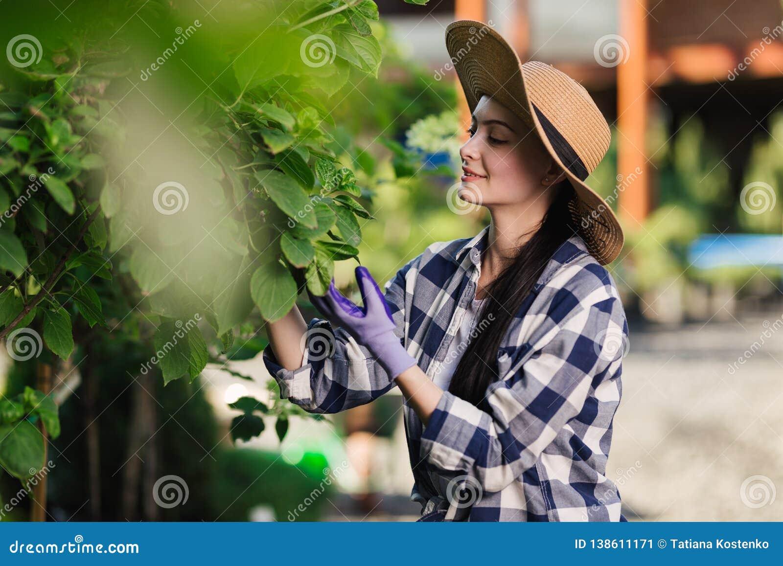 Härlig ung kvinna i rutig skjorta- och sugrörhatt som utanför arbeta i trädgården på sommardagen