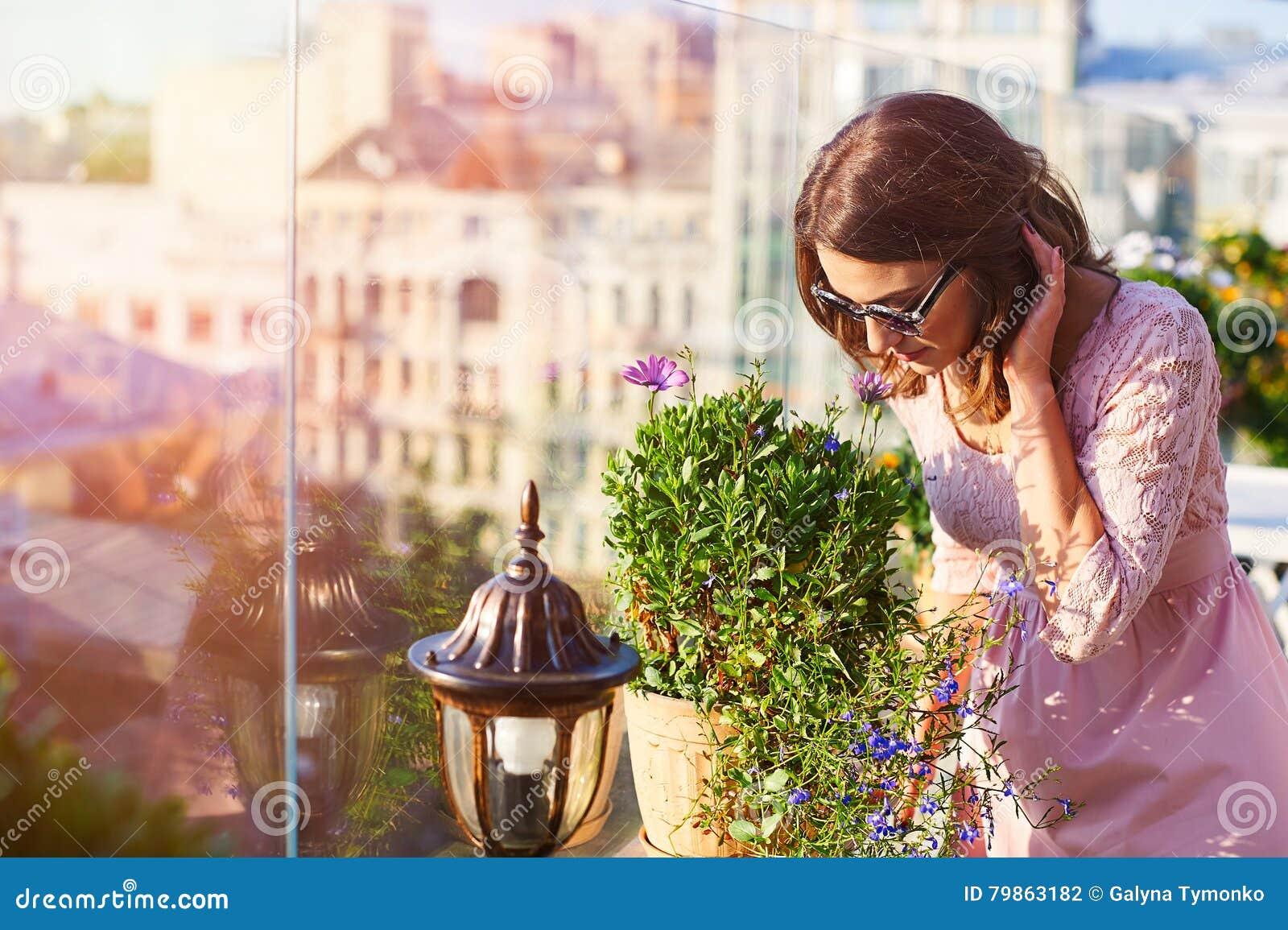 Härlig ung kvinna i solglasögon som luktar blommorna i kafé