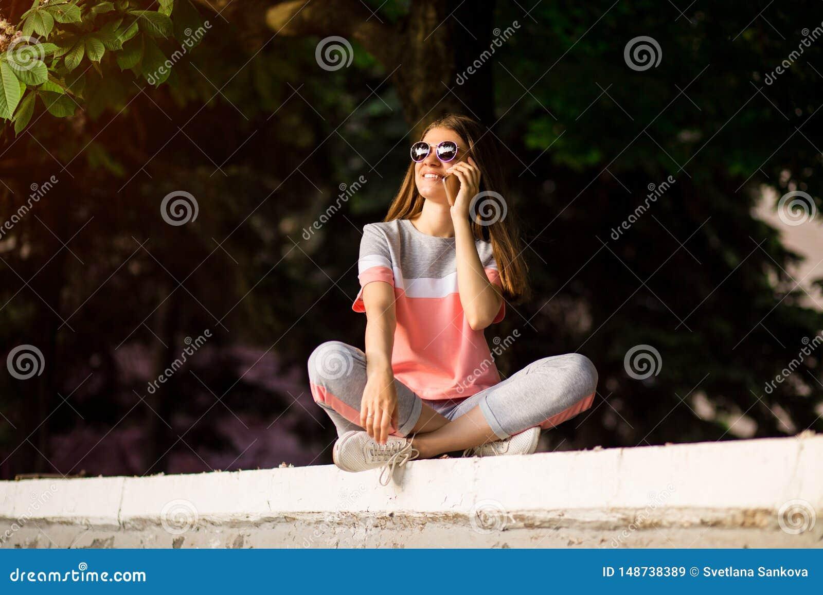H?rlig ung kvinna i solglas?gon som talar p? telefonen med leende p? framsida p? gatan