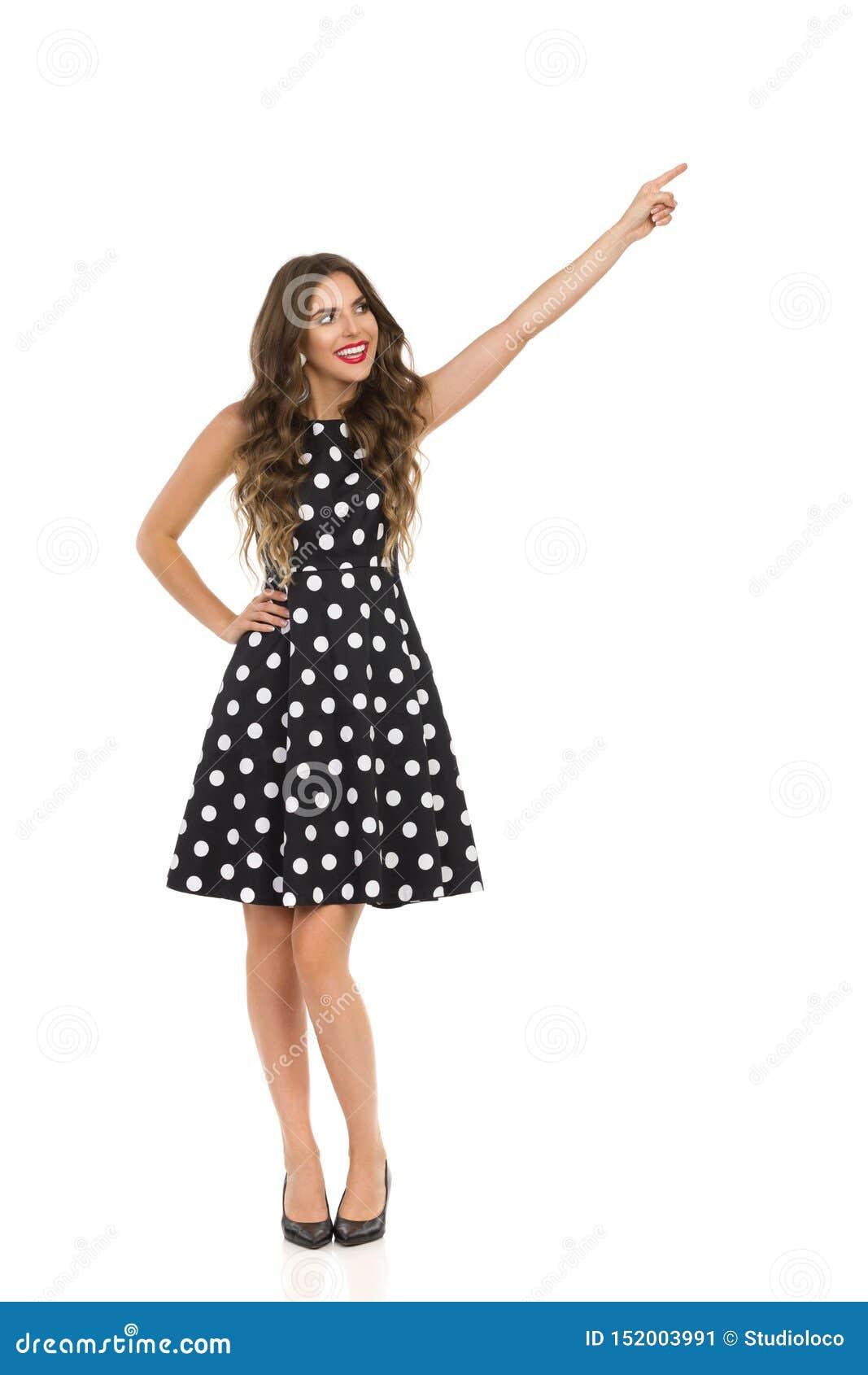 Härlig ung kvinna i svart coctailklänning i polkan Dots And High Heels Is som bort pekar och ser