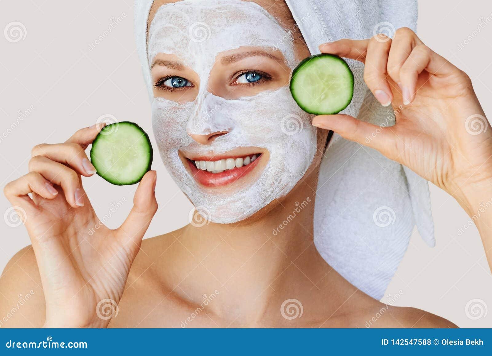 Härlig ung kvinna med den ansikts- maskeringen på hennes framsida som rymmer skivor av gurkan Hudomsorg och behandling, brunnsort