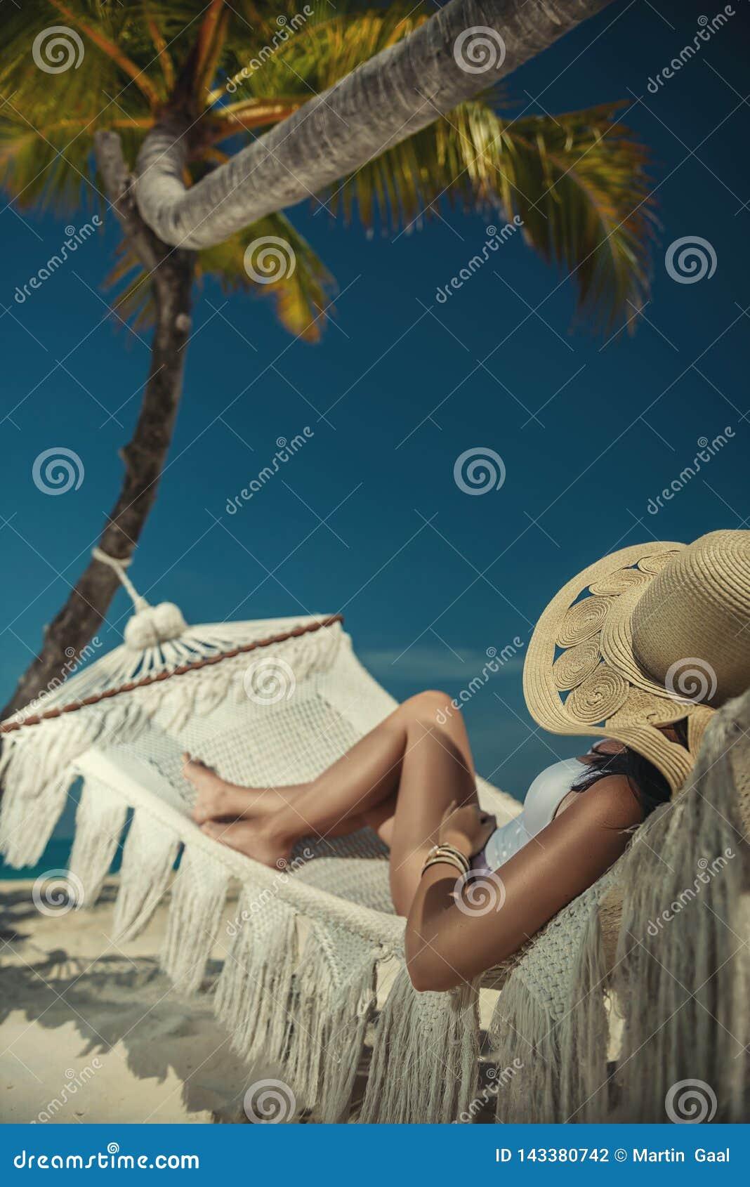 Härlig ung kvinna med hatten på den vita stranden, härligt landskap med kvinnan i Maldiverna, tropiskt paradis