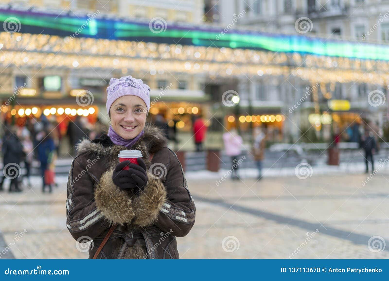 Härlig ung kvinna med kaffekoppen i staden Härlig kvinna med kaffe på gatan i vinterkläder Kvinna som har varmt