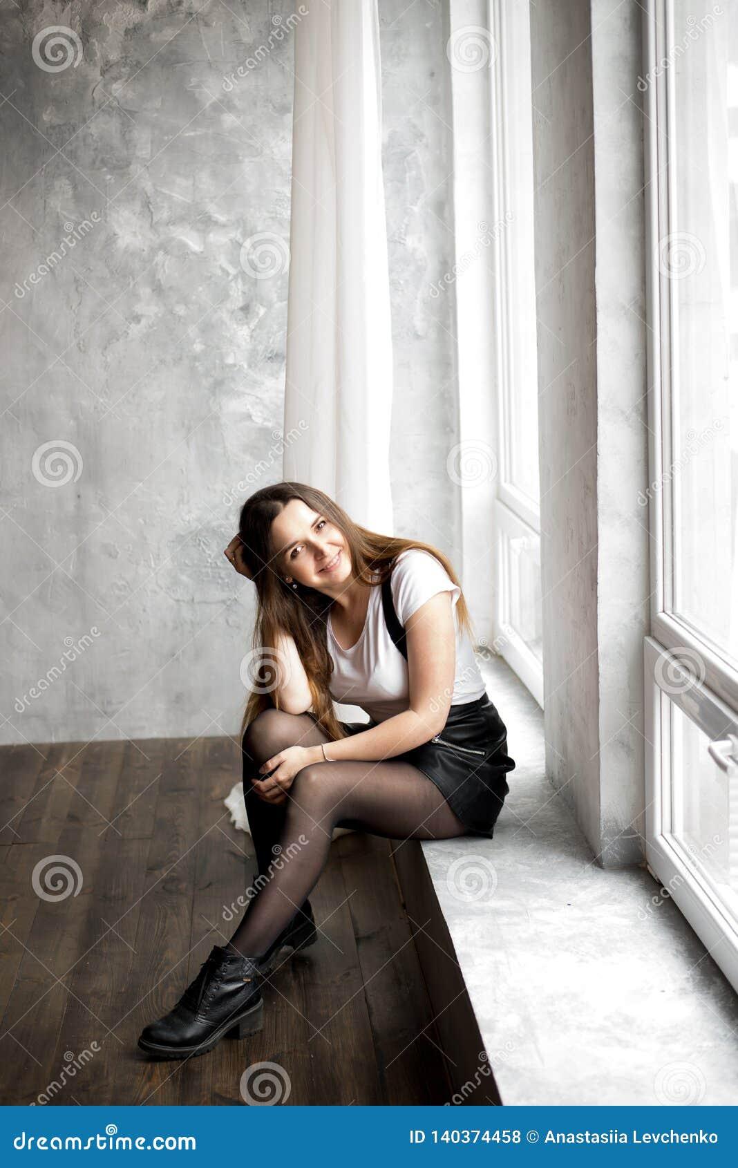Härlig ung kvinna med långt hår som sitter på fönsterfönsterbräda i rum med turkosväggen Hon är le och tycka om tid
