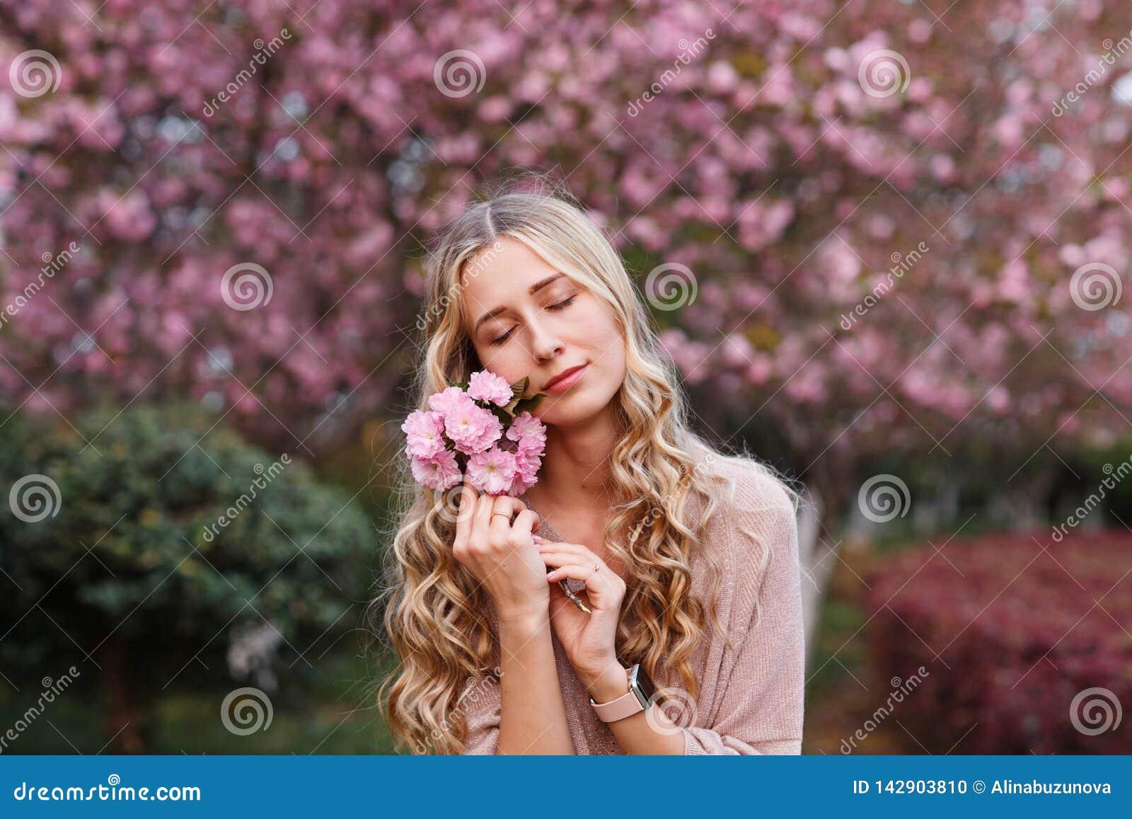 Härlig ung kvinna med långt lockigt blont hår och stängda ögon som rymmer att blomma filialen av det sakura trädet
