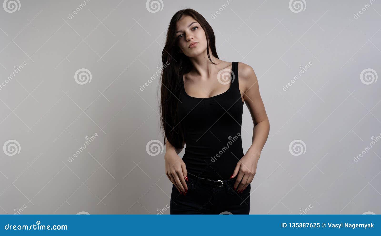 Härlig ung kvinna med långt svart hår som poserar på vit bakgrund