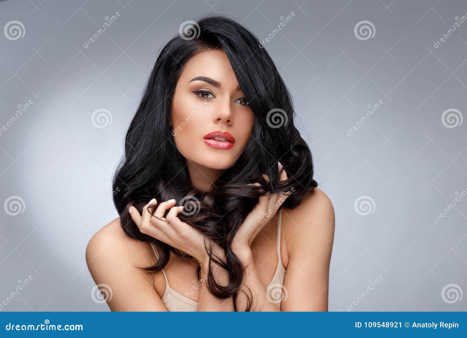 Härlig ung kvinna med rent sunt lockigt hår