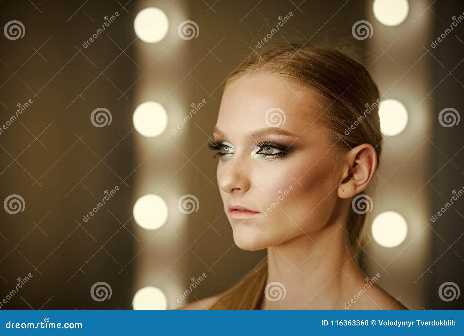Härlig ung kvinna med skinande hår och ljus makeup Livsstil och skönhetsmedelbegrepp, studio