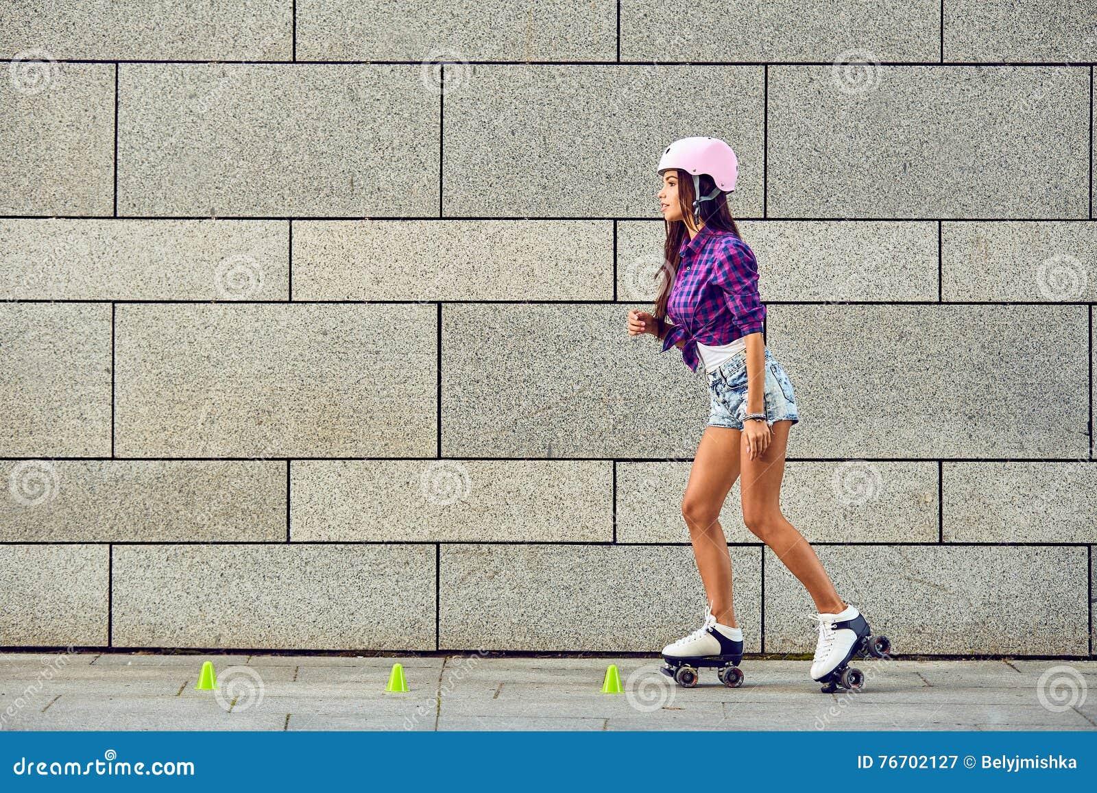 Härlig ung kvinna på rullskridskor och en rosa hjälm