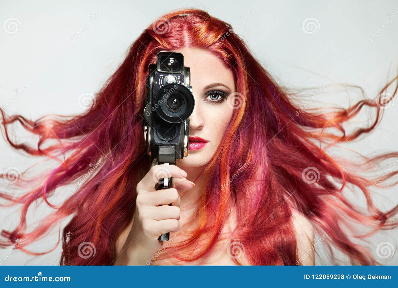 Härlig ung kvinna som använder en retro videokamera