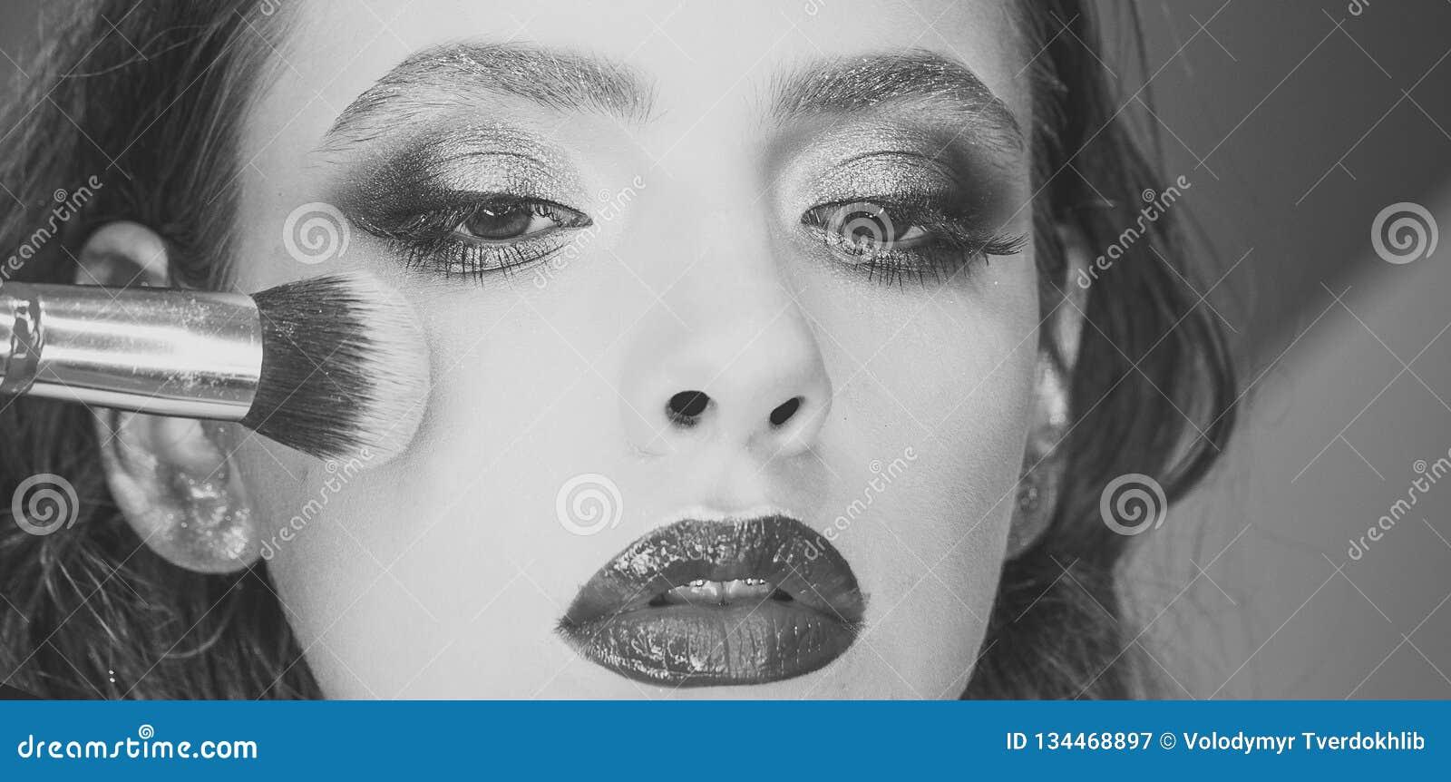 Härlig ung kvinna som applicerar kosmetiskt pulver på framsida med tofsen, begrepp för hudomsorg, fotosättning av brunetten