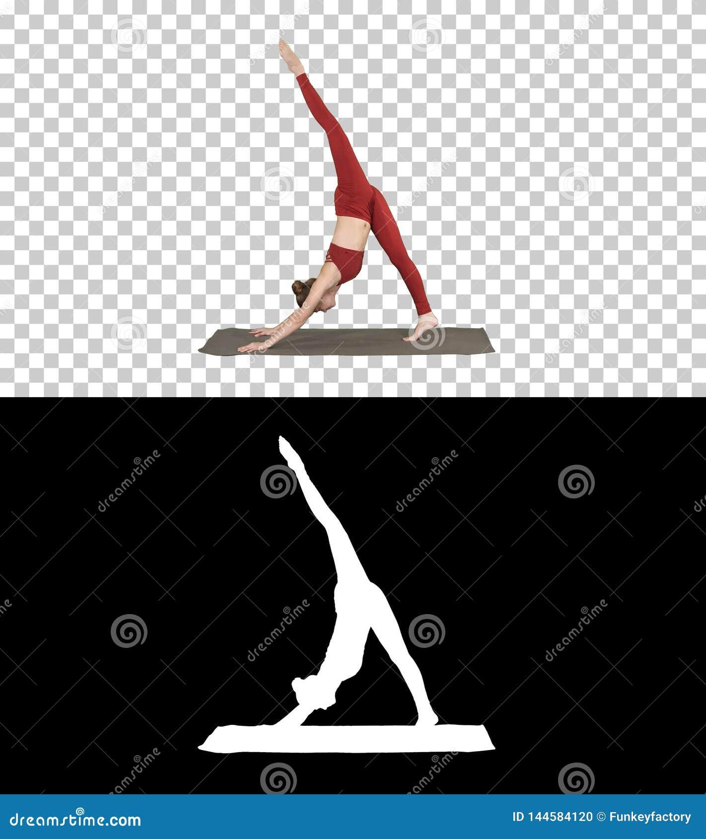 Härlig ung kvinna som bär den röda sportswearen som gör yoga- eller pilatesövningen som står i variation av Natarajasana, alfabet